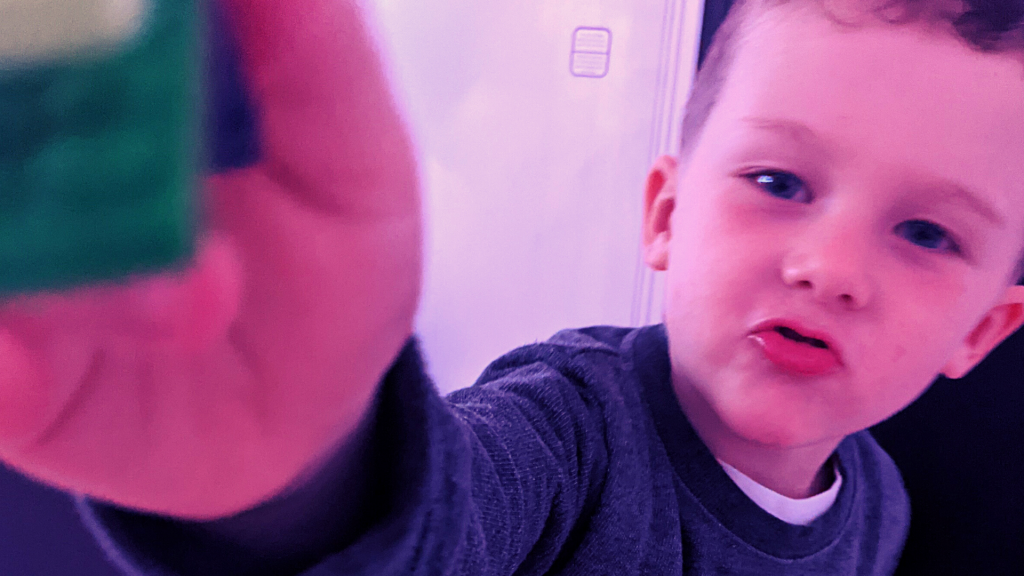 A toddler holds a Lego toy up to the camera.