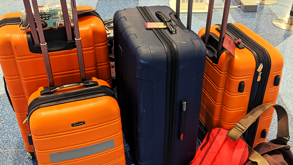 Three large suitcases, two smaller suitcases, and two backpacks sitting on the floor at the airport.