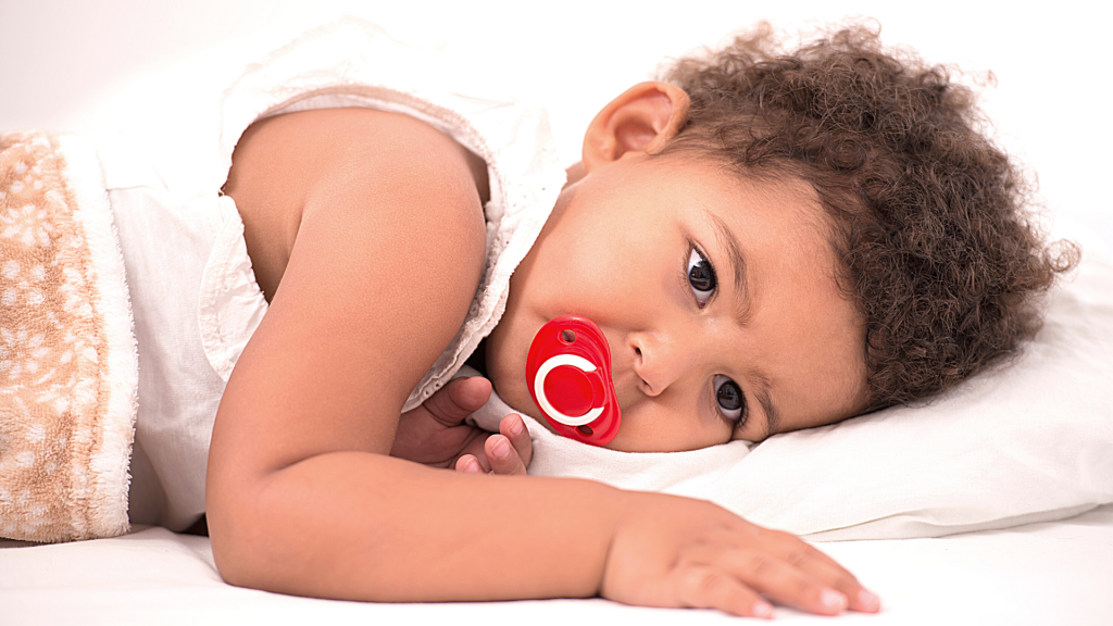 A toddler is resting on a white bed.